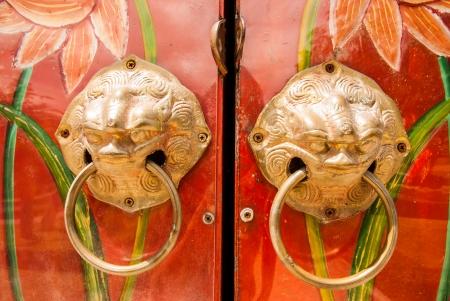 Golden handle on the door of chinese shrine photo