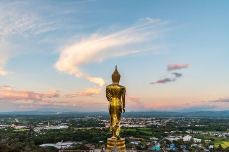 rear view of golden Buddha statue with city view background at  Phra That Khao Noi temple, Nan province, Thailand