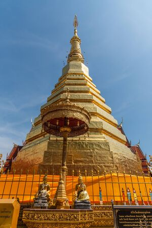 The golden pagoda with blue sky background. at Wat Prathat Cho Hae  temple, Prae province, Thailand.