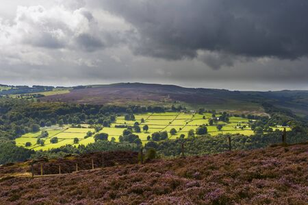 A patch of sunlight breaks through the clouds and shines on fields in the Derbyshirer countryside. photo