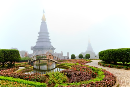 phon: flower garden and stupa in the morning mist, chiang mai, thailand Stock Photo