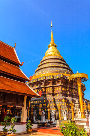 Golden pagoda in ancient buddhist temple at Lampang Province, Thailand photo