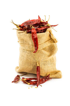 burlap sac: Dried chilli in a ramie sac on white background