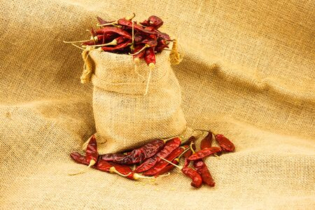 burlap sac: Dry red chili in remie sac on brown texture cloth