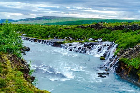 seeping: Hraunfossar or Lava Falls is a beautiful waterfalls in the West Iceland. Stock Photo