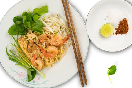 Thai style stir fried rice noodles with shrimps and vegetables on white background