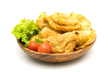 Curry Puffs, Tomatoes and Lettuce in a wooden bowl on white background Stock Photo