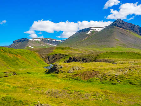 Vue sur la montagne, la vallée et le ruisseau dans le ciel bleu en été en Islande