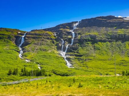 High waterfalls along the way in summer season of Green Iceland