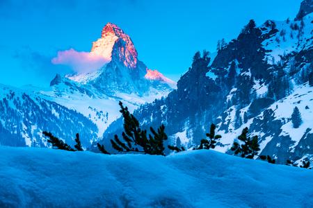 Alpine landscape with golden glow on the Matterhorn Peak at sunrise in Zermatt Switzerland