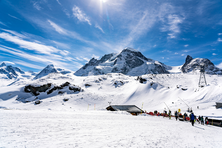 ZERMATT, SWITZERLAND - MARCH 27, 2018 : Mountaineous landscape in the Alps of Switzerland with the skiers walking at the ski tracks Publikacyjne