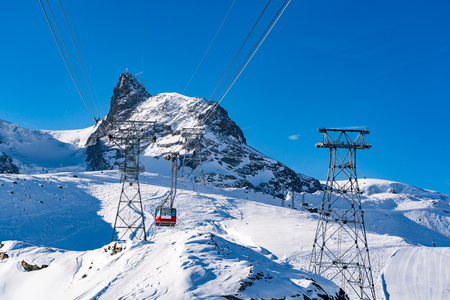 Beautiful view of Alps covered with snow and red cable car to Matterhorn peak in Zermatt Switzerland