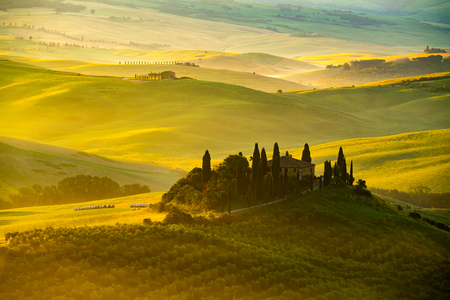 View of beautiful hilly Tuscan field in the golden morning light with farm house Cypress tree and hay bales in Valdorcia Italy Foto de archivo