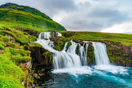 View of Kirkjufellsfoss Waterfalls at Kirkjufell Mountain in the summer rainy day at Grundarfjordur in West Iceland