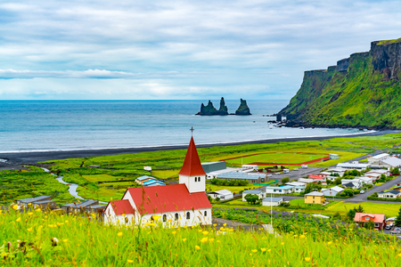 View of Reyniskirkja Church in Vik of Iceland with beautiful yellow flowers field in the foreground and Reynisdrangar rock formation in the background