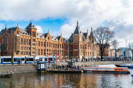 AMSTERDAM, NETHERLANDS - MARCH 4, 2016 : View of Central Railway Station and the Old Town Canal in Amsterdam, Netherlands