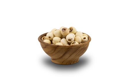 Dried Lotus Seeds in wooden bowl on white background . Nowadays lotus seed become popular healthy food and highly beneficial for health.