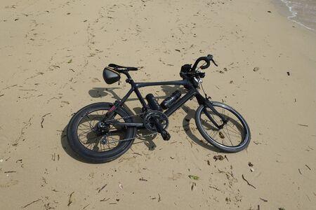 velo: a black carbon bike laid on sand beach in Ishigaki island, Okinawa, Japan Stock Photo