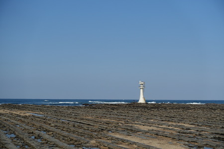 washboard: A lighthouse in eastern part of Aoshima Island at opposite side of Aoshima at the Shrine, surrounded Devils Washboard in Miyazaki, Japan