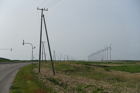 kinetic energy: power poles and a wind farm, a row of big wind turbines for electrical generation along Ororon line in in Hokkaido, Japan Stock Photo