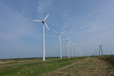 kinetic energy: a wind farm, a row of big wind turbines for electrical generation along Ororon line in in Hokkaido, Japan