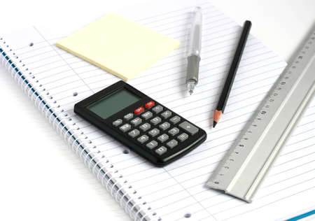 calculator pen pencil and ruler on white lined notepad