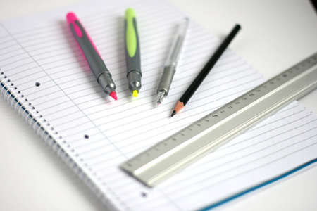 pens pencil and ruler on white lined notepad with small depth of field Stock Photo