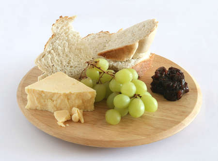bread cheese pickle and grapes on wooden board