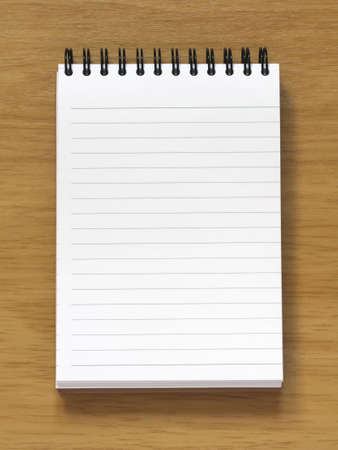 empty spiral notebook on wooden desk background. Add your own text