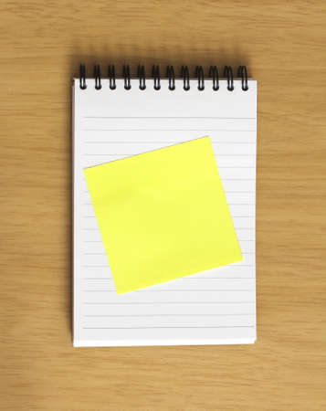 blank yellow postit stuck to spiral notebook on wooden desk background. Add your own text