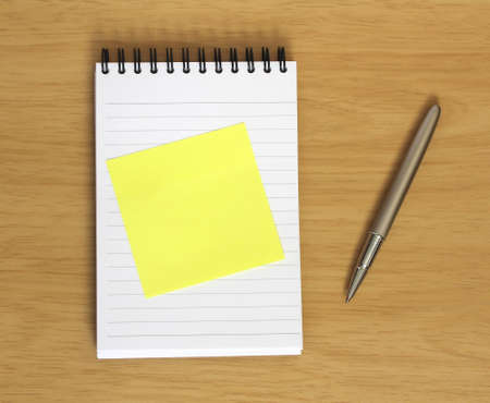blank yellow postit stuck to spiral notebook with pen on wooden desk background. Add your own text
