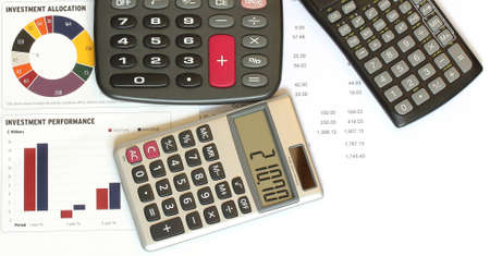 three calculators on print out of financial figures and graphs Stock Photo