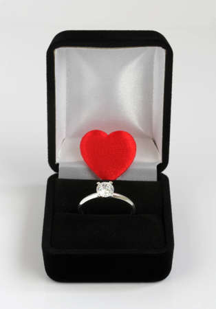 diamond engagement ring in black velvet case with a small red valentines love heart Stock Photo - 8889239