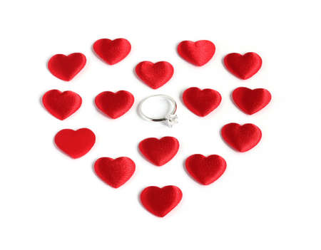 diamond ring inside large heart shape made from many red hearts isolated on white background Stock Photo