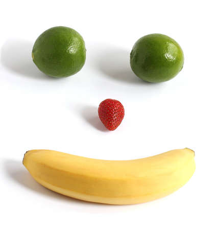happy face made from banana strawberry lime fruit isolated on white background