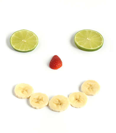 happy smiley face made from sliced banana strawberry lime fruit isolated on white background