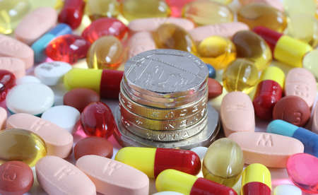 money coins surrounded by pills tablets and capsules Stock Photo