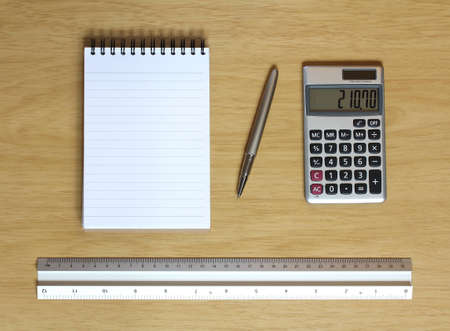 notebook calculator metal ruler and pen all on a wooden desk Stock Photo