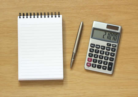 spiral notebook showing empty page with pen and calculator on wooden desk