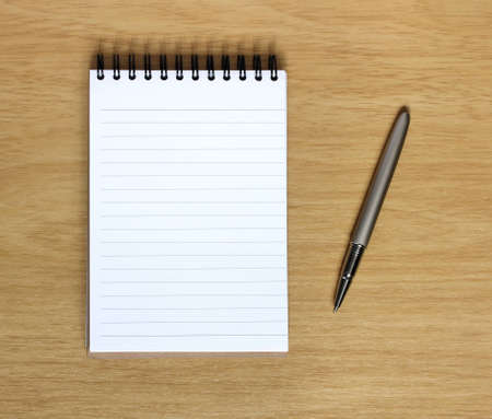 empty notebook with pen next to it on wooden desk Stock Photo