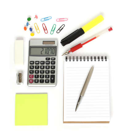 stationery supplies consisting of calculator notepad pens sticky notes paperclips drawing pins sharpener and eraser isolated on white background photo