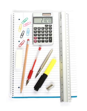 stationery supplies consisting of calculator ruler pens pencil sharpener eraser and paperclips on a large spiral notebook isolated on white background