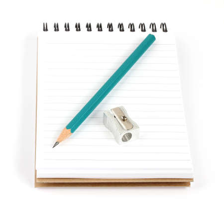 pencil and sharpener on a notebook isolated on white background