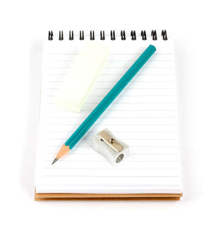 pencil sharpener and eraser on a spiral notepad isolated on white background photo