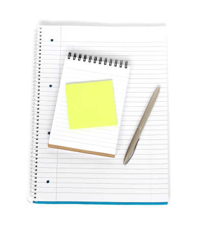 blank sticky note on a notepad with pen on a notebook isolated on white background