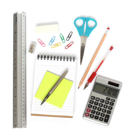 stationery supplies consisting of ruler notepad calculator pens pencil sharpener eraser paperclips scissors and sticky notes isolated on white background photo