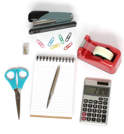stationery supplies consisting of stapler scissors notebook pen calculator paper clips and pencil sharpener isolated on white background