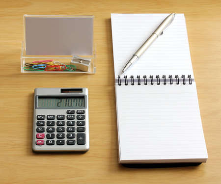 notebook with pen calculator with paper clips and pencil sharpener in a business card holder on a wooden desk Stock Photo