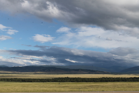 Wide steppe with yellow grass under a blue sky with white clouds Sayan mountains Siberia Russia. beautiful hill