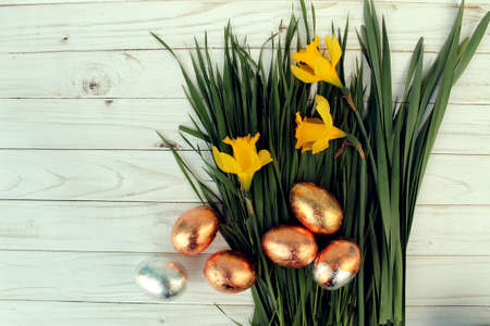 Easter golden eggs and daffodils on wood background